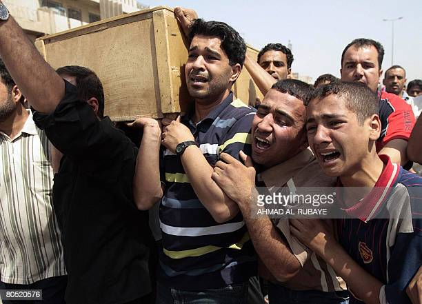 Iraqi Shiite men weep as they carry the coffin of an Iraqi man killed in an alleged raid by US forces during his funeral procession in Baghdad's...