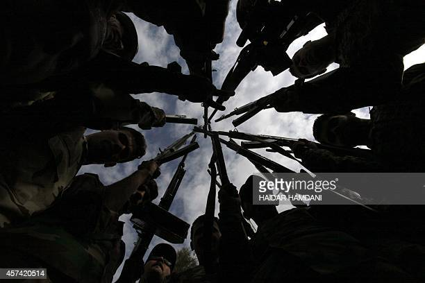 Iraqi Shiite men who have volunteered to join government forces and militias in the fight against jihadists from the Islamic State group, take part...