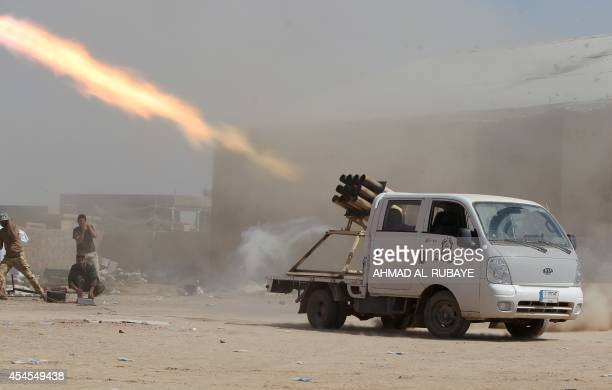 Iraqi Shiite militia fighters fire a rocket at Islamic State militant positions at Sayed Hassan village outside the city of Tikrit on September 3...
