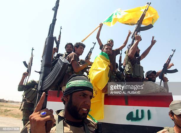 Iraqi Shiite militia fighters raise up their weapons as they celebrate pushing back Islamic State militants on September 3 on the road between Amerli...