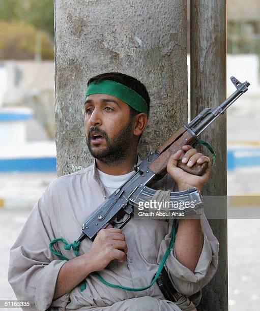 Iraqi Shiite militia man loyal to the radical cleric Moqtada al-Sadr takes cover behind a concrete column as a US tank fires at the militia positions...