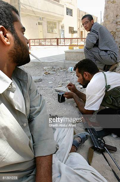 Iraqi Shiite militia man try to set an Improvised Explosive Devise under advancing US tanks August 21 2004 in Najaf Iraq The militia loyal to the...