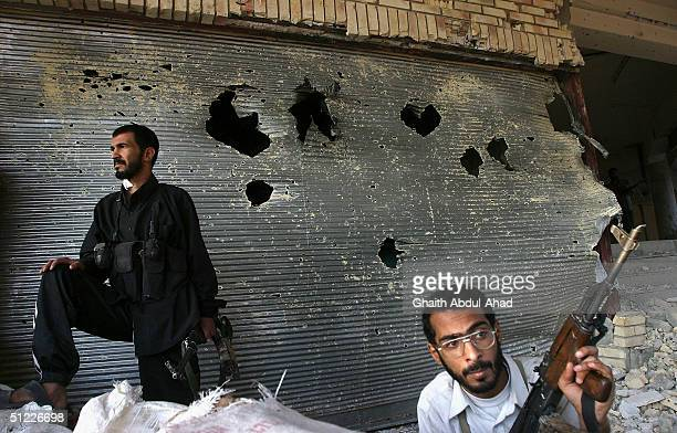 Iraqi Shiite militia men guard the street leading to the shrine of Imam Ali in Najaf just before the end of a dead line to hand weapons to the Iraqi...