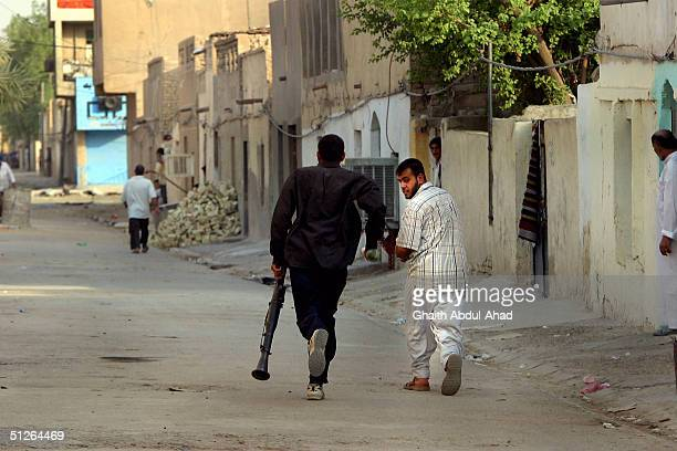 Iraqi Shiite militia men run down an alleyway looking for US tanks in the Shiite area of Sadr city east of Baghdad on September 5 2004 US forces...