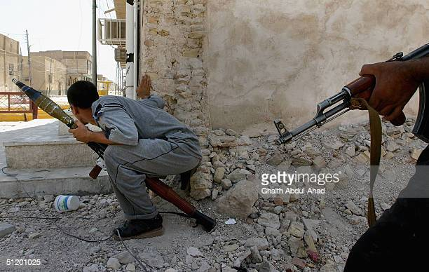 Iraqi Shiite militia men take a look out from behind a corner at advancing US tanks August 21 2004 in Najaf Iraq The militia loyal to the radical...
