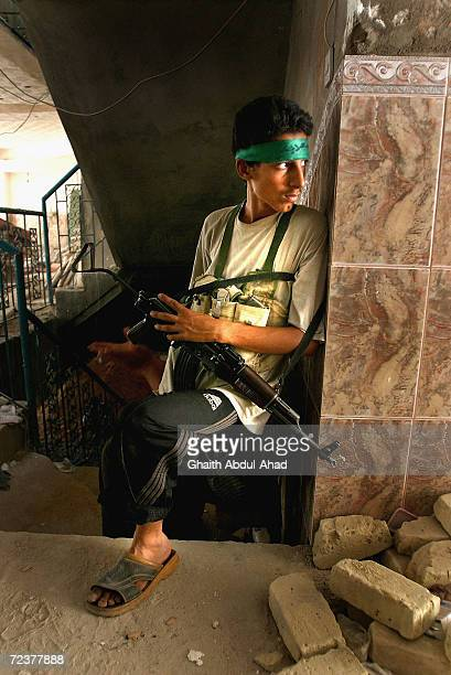 Iraqi Shiite militia men take cover inside a building on the eastern front lines of the old town on August 24 2004 in Najaf Iraq The militia men were...