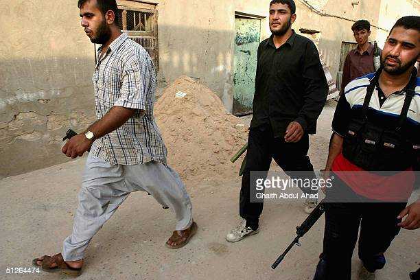 Iraqi Shiite militia men walk down an alleyway looking for US tanks in the Shiite area of Sadr city east of Baghdad on September 5 2004 US forces...