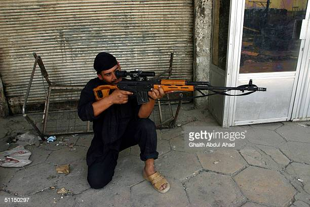 Iraqi Shiite militiaman aims his rifle during clashes with US Marines August 7 2004 in Najaf Iraq Fighting continued for the third day between Iraqi...
