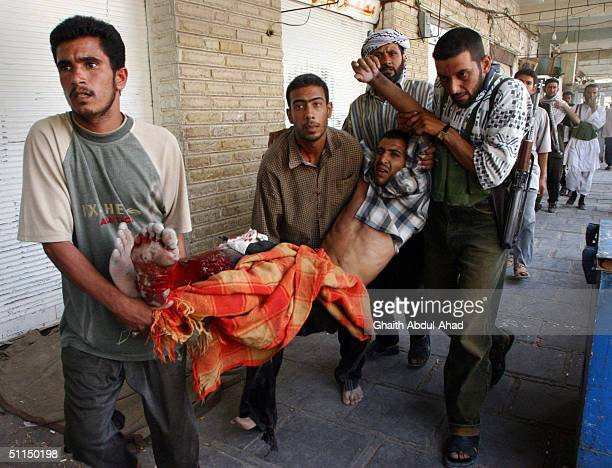 Iraqi Shiite militiamen carry Ihssan Ali a fighter who was wounded during clashes with US Marines August 7 2004 in Najaf Iraq Fighting continued for...