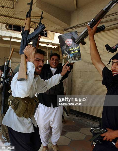 Iraqi Shiite militiamen hold up their weapons and a poster of Moqtada alSadr as they celebrate the news of clashes with US Marines August 7 2004 in...