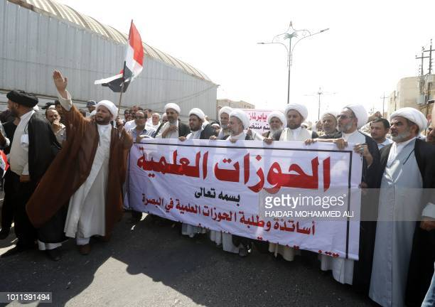 Iraqi Shiite Muslim clerics hold a banner with the name of a religious school that was attacked by protesters in Iran the day before during an...