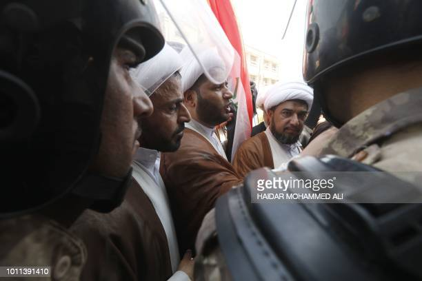 Iraqi Shiite Muslim clerics protest as security forces form a human barrier during ongoing protests in the southern city of Basra on August 5 2018...