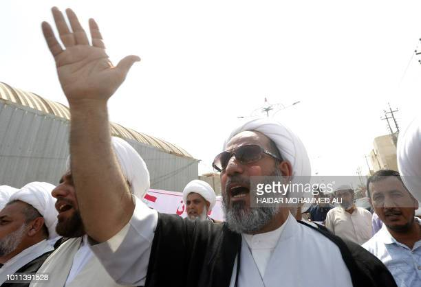Iraqi Shiite Muslim clerics shout slogans during ongoing protests in the southern city of Basra on August 5 2018 Iraq has been gripped by protests...