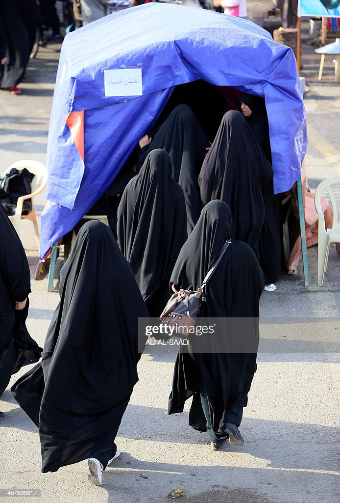 Iraqi Shiite Muslim pilgrim women enter a tent to undergo security check at a checkpoint as they walk along the main highway that links the Iraqi capital ... & Iraqi Shiite Muslim pilgrim women enter a tent to undergo security ...