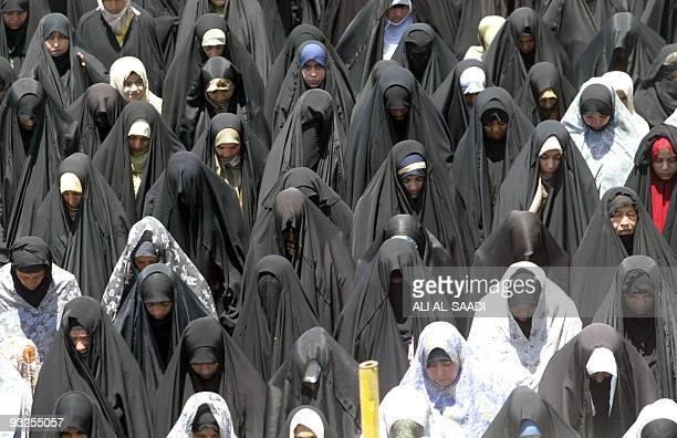 Iraqi Shiite Muslim women wearing the black Abaya stand under the blazing noon sun as they take part in Friday prayers 10 June 2005 Across the Muslim...