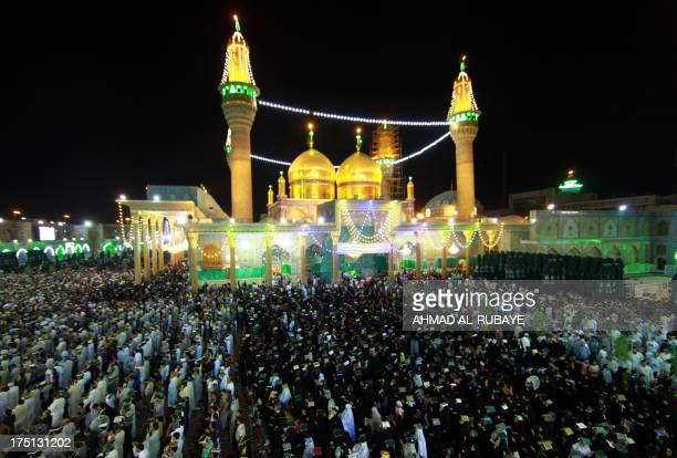 Iraqi Shiite Muslim worshipers place the Koran over their heads as they attend a Lailat alQadr or Night of Destiny prayer in the Imam Musa alKhadim...