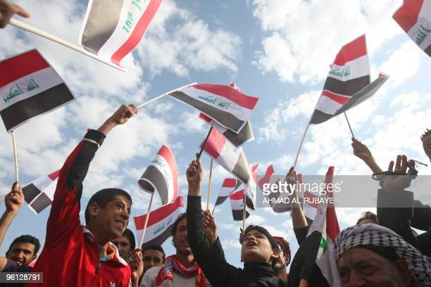 Iraqi Shiite Muslim youth wave their national flag during a protest against the earlier visit of US Vice President Joe Biden and against the Baath...