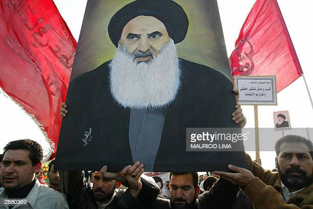 Iraqi Shiite Muslims hold up a portrait of leading Shiite cleric Grand Ayatollah Ali al-Sistani as thousands stage a demonstration in the centre of...