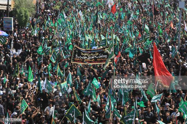 Iraqi Shiite Muslims take part in a mourning procession on the tenth day of the lunar month of Muharram which marks the day of Ashura, in the holy...