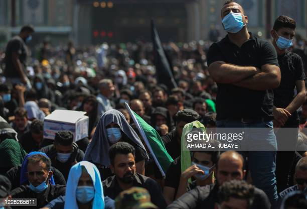 Iraqi Shiite Muslims take part in a mourning ritual on the tenth day of the month of Muharram which marks the peak of Ashura, amid the COVID-19...