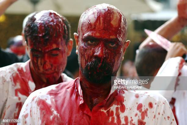 Iraqi Shiite Muslims take part in a traditional mourning event during Ashura commemorations that mark the killing of Imam Hussein one of Shiite...