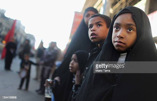 Iraqi Shi'ite Muslims watch a parade marking the month of Muharram in preparation for the festival Ashura on December 1 2011 in Baghdad Iraq Ashura...