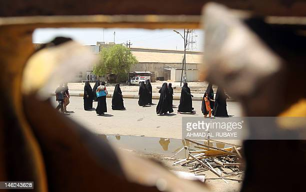 Iraqi Shiite pilgrims heading to Kadhimiya walk past the site of a roadside bomb in Baghdad's Karrada district on June 13 2012 as a wave of bombings...