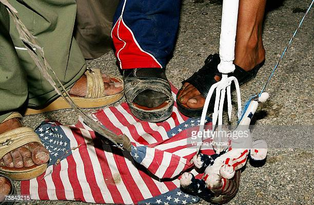 Iraqi Shiite step on an American flag during an antiUS protest called by firebrand Shiite cleric Moqtada alSadr to mark the fourth anniversary of the...