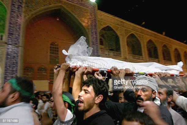Iraqi Shiite supporters of the radical cleric Moqtada alSadr carry the body of a militia fighter killed in the fighting with US troops during a...