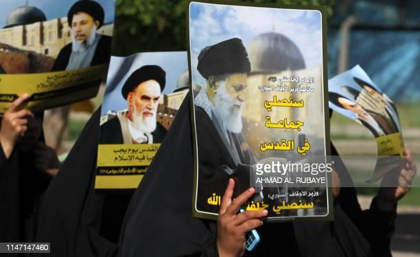 Iraqi Shiite women carry portraits of Iran's Supreme Leader Ali Khamenei his predecessor and Islamic Revolution founder Ayatollah Ruhollah and late...