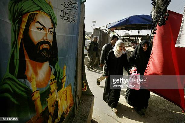 Iraqi Shiite women walk past a flag bearing the image of Imam Hussein hanged on a concrete wall to celebrate Ashura on December 30 2008 in Baghdad...