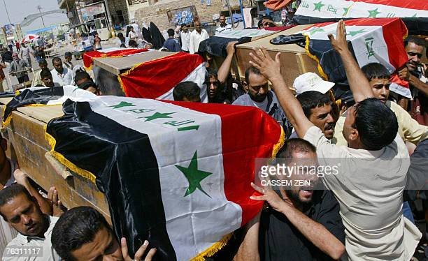 Iraqi Shiites carry coffins during the funeral for the thirteen people killed in Baghdad's northwestern neighbourood of Shuala in overnight clashes...