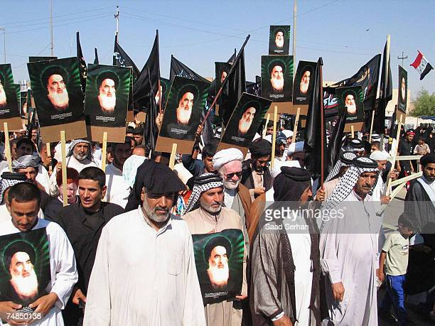 Iraqi Shiites carry pictures of influential cleric Grand Ayatollah Ali al-Sistani during a protest on June 21, 2007 in the holy Shiite city of Najaf...
