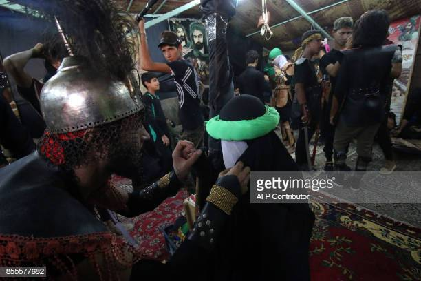 Iraqi Shiites get dressed ahead of a reenactment of the Battle of Karbala ahead of the religious festival of Ashura during which they mourn the...