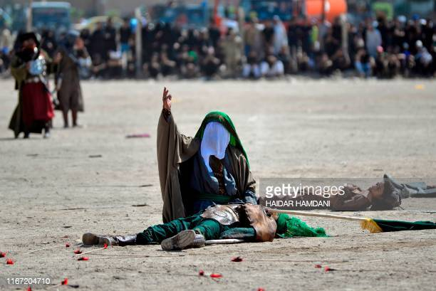 Iraqi Shiites in costumes re-enact events of Ashura in the central city of Najaf during the mourning procession on the tenth day of Muharram which...