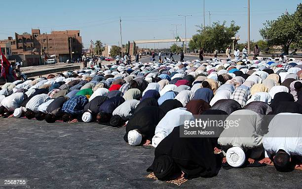 Iraqi Shiites pray in the middle of the blocked airport road during a protest against the detention of local Shia Imam Mo'ayed alKhezragi by US...
