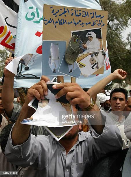 Iraqi Shiites tear up pictures of Qatari Emir Sheikh Hamad al-Thani as they protest against the Doha-based satellite Arab channel Al-Jazeera, 04 May...