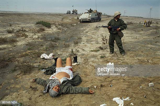 Iraqi soldier lying on the ground with his arms outstretched some of his clothes off and his shirt open to show he means no harm and is surrendering...