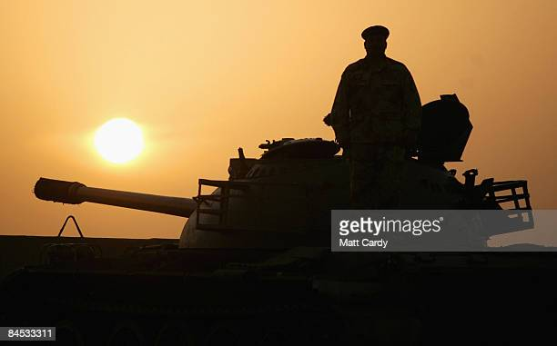 Iraqi soldier watches the sunrise from the top of his armoured tank as he protects the perimeter of the Basra Operations Centre headquarters on...