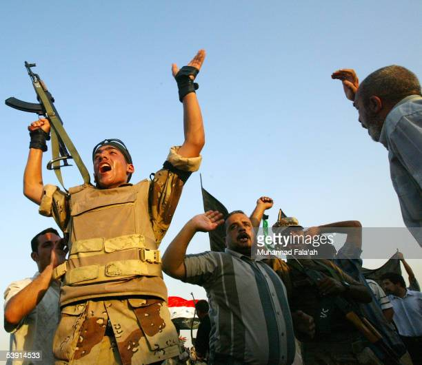 Iraqi soldiers and civilians shout after gunfire erupted on a bridge September 1 2005 in Baghdad Iraq Gunfire erupted as Shiite protesters marched...