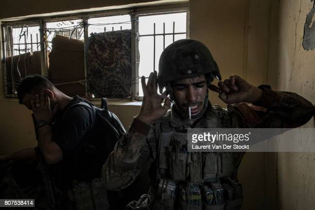 Iraqi soldiers brace themselves as they detonate an explosive to clear a passage in alNuri mosque district of Mosul's Old City on June 29 2017 The...