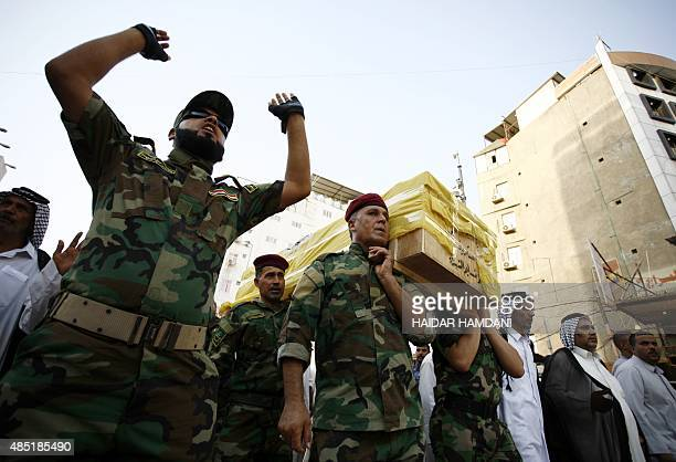 Iraqi soldiers carry the coffin of an Iraqi fighter who belonged to Iraq's Popular Mobilisation units and was killed in the town of Baiji during...