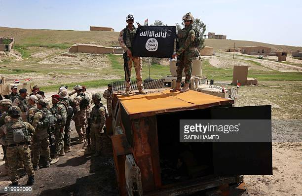 Iraqi soldiers celebrate with a flag that they seized from the Islamic State group as they hold a position near the frontline on April 9 2016 in the...