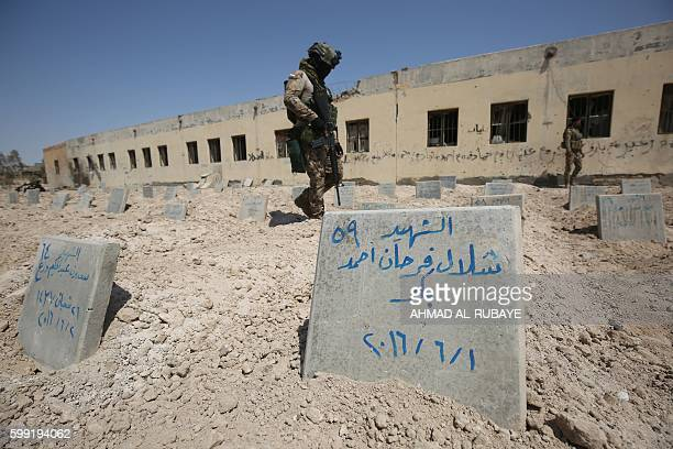 TOPSHOT Iraqi soldiers check a cemetary where jihadists of the Islamic State group were buried by the group on September 4 2016 in Fallujah Iraq's...