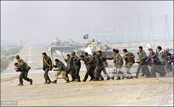 Iraqi soldiers cross a highway carrying white surrender flags 25 February 1991 in Kuwait City Iraq's invasion of Kuwait 02 August 1990 ostensibly...