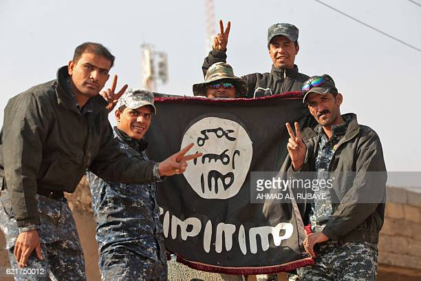 Iraqi soldiers display a captured flag of the Islamic State in the Hamam alAlil area about 14 kilometres from the southern outskirts of Mosul on...