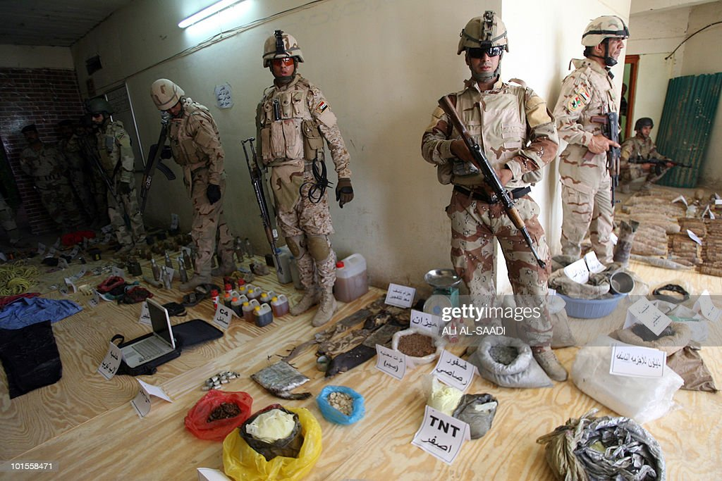 Iraqi soldiers display weapons and materials used for making bombs they found at the house of a man who allegedly makes them in the area of Sabaa al-Bor, north of Baghdad, on June 2, 2010 after the suspect who was wearing an explosive belt blew himself up when security forces surrounded his house.