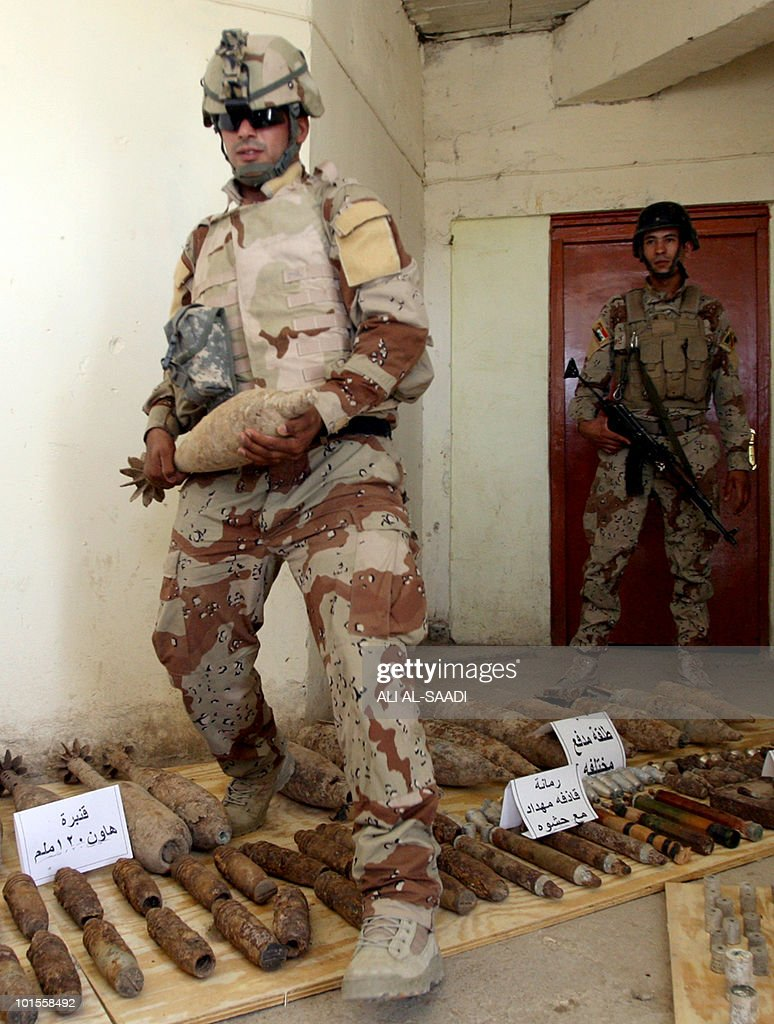 Iraqi soldiers display weapons seized at the house of a man who allegedly makes car bombs in the area of Sabaa al-Bor, north of Baghdad, on June 2, 2010 after the suspect who was wearing an explosive belt blew himself up when security forces surrounded his house.