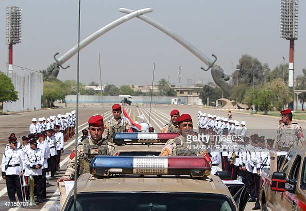 Iraqi soldiers drive in front of the Swords of Qadisiyah in Baghdad on April 29 during the funeral for the bodies of the victims believed to be...