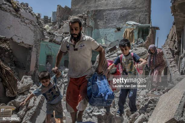 Iraqi soldiers escort families emerging from buildings in alNuri mosque complex on June 29 in Mosul Iraq The Iraqi Army Special Operations Forces and...